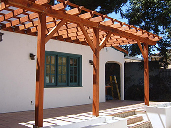 A Construction Heart redwood pergola attached to a Spanish style home.