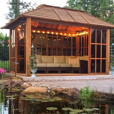 A redwood gazebo with outdoor furniture and mood lights.