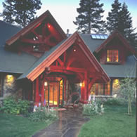 The welcoming entrance of a large home makes beautiful use of redwood timbers and redwood siding.
