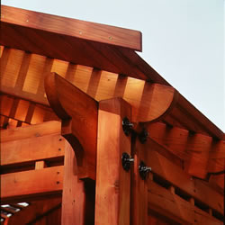 The corner detail of an outdoor room where redwood posts, beams and rafters meet. The ends of the rafters and beams are shaped with graceful curves.
