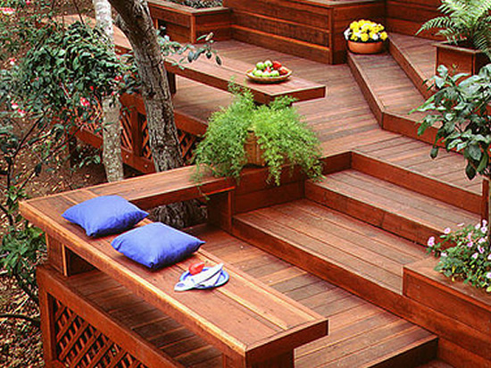 A multi-level deck, with steps and built-in benches, made from redwood lumber.