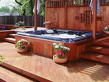 Redwood deck, steps and fence surround a backyard spa.