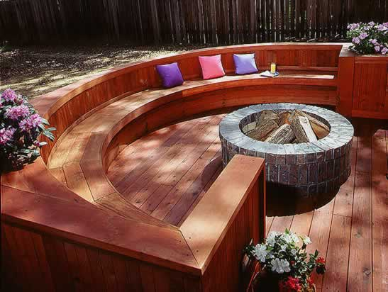Curved redwood bench arcs around a stone firepit.