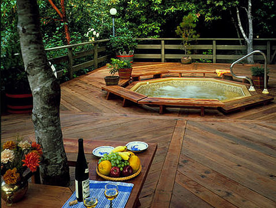 Redwood decking applied in a herring bone pattern surround an octagonal spa.