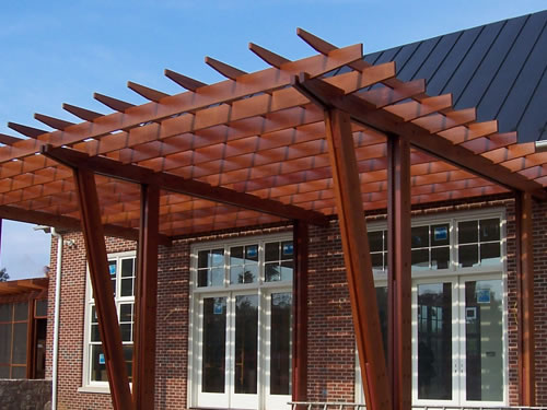 Redwood beams used in a handsome shade structure on the side of a home.