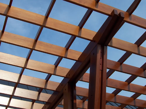 A shade structure made from redwood timbers and boards.