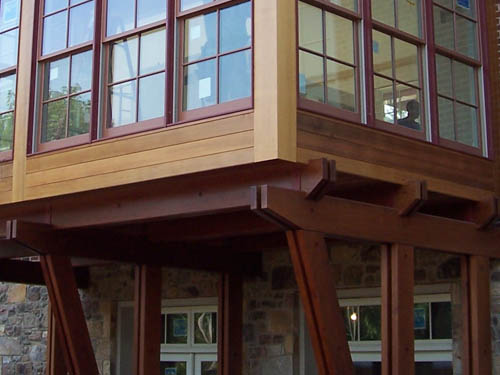 Redwood beams support a windowed room that bumps out from the main structure.