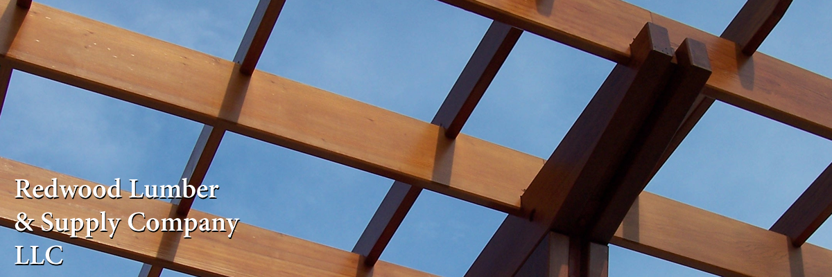 Redwood timbers used in a shade shelter. The ends of the redwood rafters are shaped in an elegant pattern.