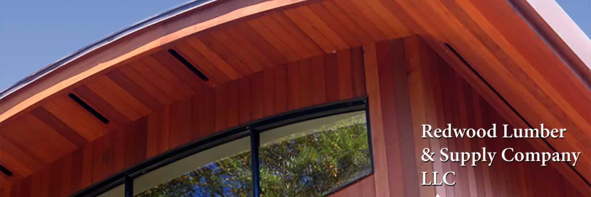 A modern house with a curved roof with redwood siding and soffits.