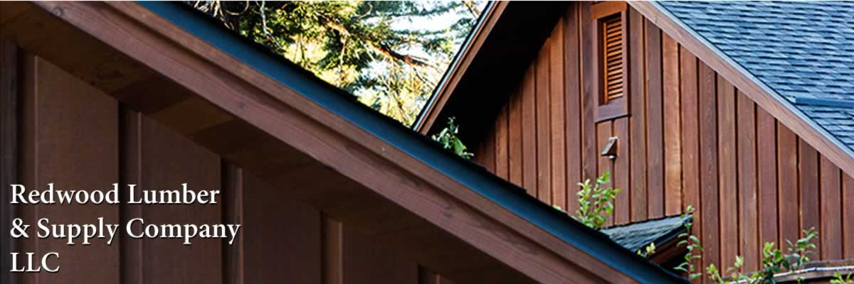 A custom house has beautiful redwood siding and soffits. The house also features custom-designed, curved windows.