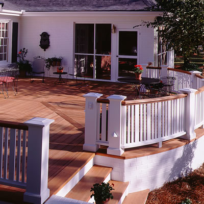 A spacious redwood deck includes a curved balustrade. The top rail of the balustrade is natural redwood, the newels and balusters are painted white.