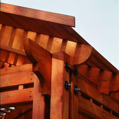 Corner of a pergola with shaped redwood beams and timbers.