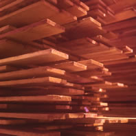 Redwood boards stacked in a pile of random lengths.