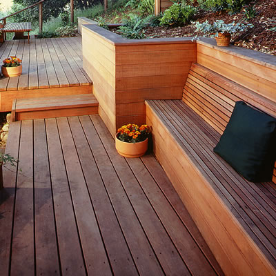 A modern redwood deck's design includes multi-levels, builtin planters, retaining walls and benches.